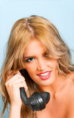 Sexy woman smiling while using a vintage telephone — Stock Photo