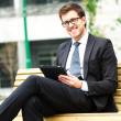 Smiling businessman using a tablet — Stock Photo