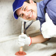 Smiling plumber at work - Stock Photo