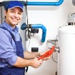 图库照片: Technicirepairing hot-water heater