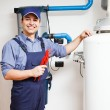 Smiling plumber at work - Stockfoto