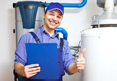 Technician servicing an hot-water heater — Stok fotoğraf