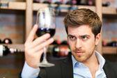 Sumiller mirando a un vaso de vino — Stockfoto