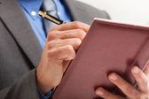Businessman writing on his agenda — Stock Photo