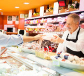 Shopkeeper serving a customer — Stockfoto