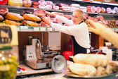 Shopkeeper at work in a grocery store — Stock Photo