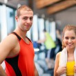 Woman and man smiling in a fitness club — Stock Photo