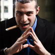 Shady man smoking a cigar - Stock Photo