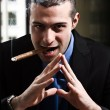 Stock Photo: Shady msmoking cigar