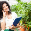 Clerk talking on the phone in a greenhouse — Stock Photo