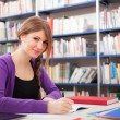 Portrait of a student in a library — Stockfoto
