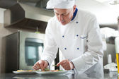 Chef garnishing a dish — Stock Photo
