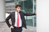 Businessman leaning on a metal column — Foto de Stock
