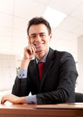 Friendly businessman sitting at his desk — Stock Photo