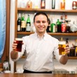 Stock Photo: Bartender serving beer