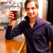 Young man having a beer in a pub — Stock Photo