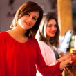 Two young women enjoying a drink in a pub — Stock Photo