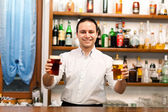 Bartender serving beer — Stock Photo