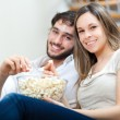 Couple eating popcorn while watching a movie — Stock Photo #30020829