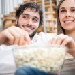 Stock Photo: Couple eating popcorn while watching a movie