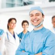Foto Stock: Smiling doctor in front of his team