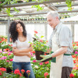 Greenhouse worker talking to a customer — Stock Photo