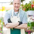 Happy gardener in a greenhouse — Stock Photo