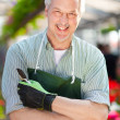 Handsome mature gardener portrait in a greenhouse — Stock Photo