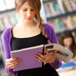 Stock Photo: Beautiful female student in a library