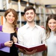 Group of students standing in a library — Stockfoto