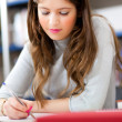 Beautiful female student in a library — Stockfoto