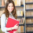 Beautiful female student in a library — Stock Photo #30027087