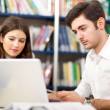 Students using her laptop in library — Stock Photo #30027249