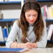 Female student in a library — Stock Photo