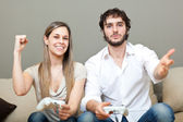 Young couple playing video games in their apartment — Stock Photo