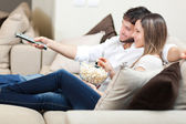 Young couple watching tv on a sofa — Stock Photo