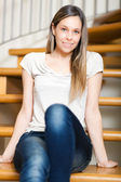 Smiling woman sitting on stairs at home — Stock Photo