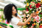 Beautiful female florist touching some flowers in a greenhouse — Stock Photo
