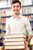 Lachende student houden een stapel van gestapelde boeken — Stockfoto