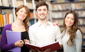 Group of students standing in a library — Stock Photo