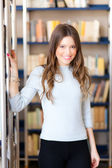 Portrait of a beautiful student in a library — Stock Photo