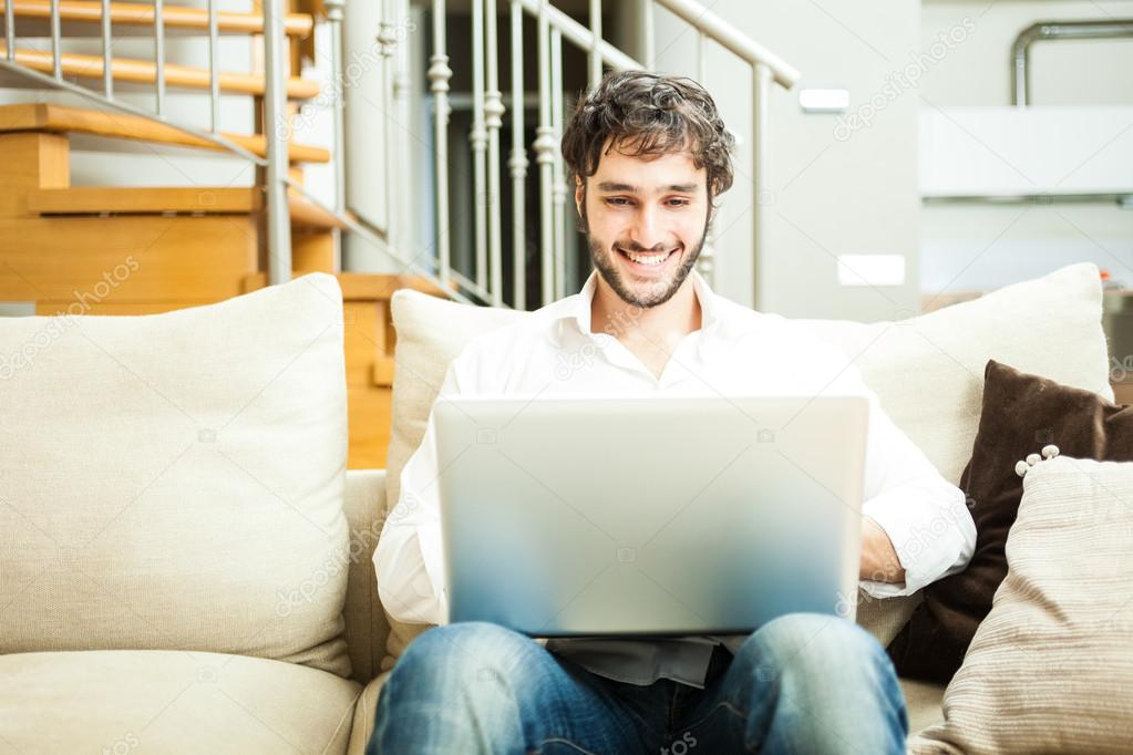 Uomo utilizzando un computer portatile nel suo ...