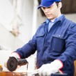 Worker grinding metal plate — Stock Photo #30136747