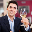 Handsome man holding a glass of wine — Stock Photo #30137933