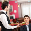 Waiter serving food to a customer — Stock Photo #30137951