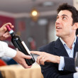 Waiter suggesting a bottle of wine to a customer — Stock Photo