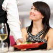Stock Photo: Waiter serving womin restaurant