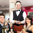 Happy couple and waiter smiling in the restaurant — Stock Photo