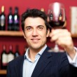 Handsome man holding a glass of wine — Stock Photo