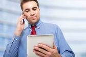 Muž mluví po telefonu při používání jeho tablet — Stock fotografie